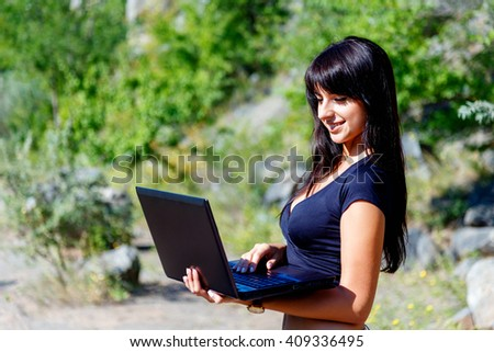 smiling brunette girl with long hair using laptop on a background of green grass. Looking to laptop, Sunny summer day