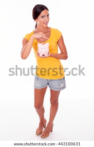 Smiling brunette holding a pink piggy bank saving coins while looking at camera and wearing a yellow t-shirt and short jeans isolated - stock photo