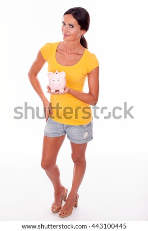 Smiling brunette holding a pink piggy bank while looking at the camera and wearing a yellow t-shirt and short jeans isolated - stock photo