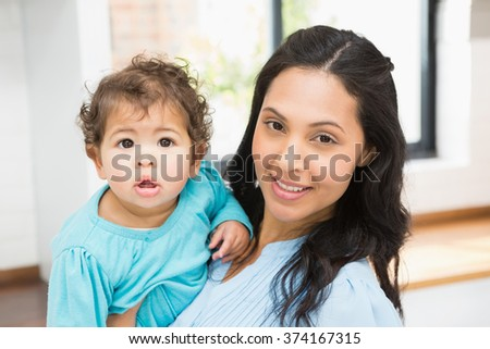 Smiling brunette holding her baby at home - stock photo