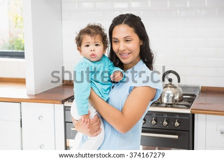 Smiling brunette holding her baby in the kitchen - stock photo