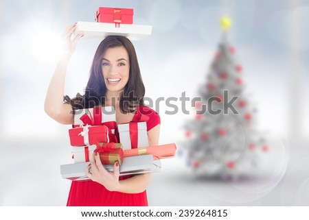 Smiling brunette holding many gifts against blurry christmas tree in room - stock photo