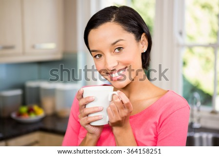 Smiling brunette holding white cup in the kitchen