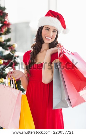 Smiling brunette in red dress holding shopping bags at home in the living room