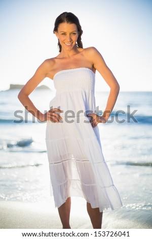 Smiling brunette in white summer dress posing on the beach at dusk - stock photo
