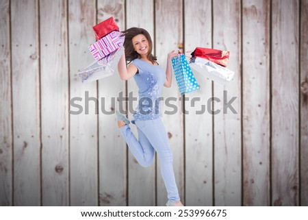 Smiling brunette jumping while holding shopping bags against wooden planks