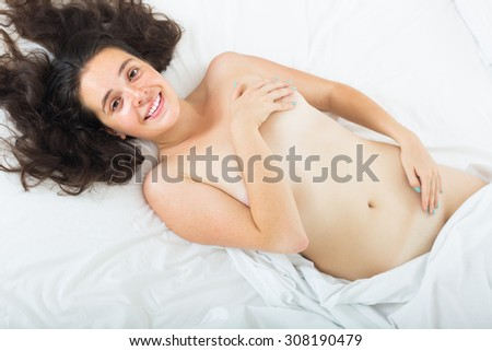 Smiling brunette nude girl lying on bed at bedroom