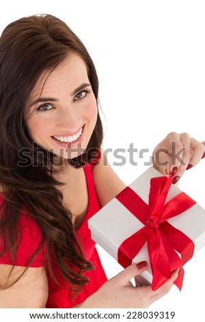 Smiling brunette opening gift on white background - stock photo