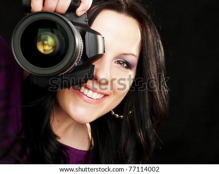 smiling brunette photographer woman holding camera over dark background - stock photo