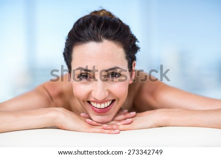 Smiling brunette relaxing on massage table in a healthy spa - stock photo