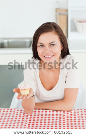 Smiling brunette showing a cupcake looking at the camera - stock photo