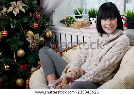 smiling brunette sitting in the armchair in christmas eve - stock photo