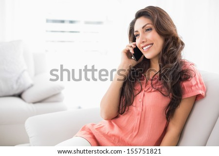 Smiling brunette sitting on her couch on a phone call at home in the living room - stock photo