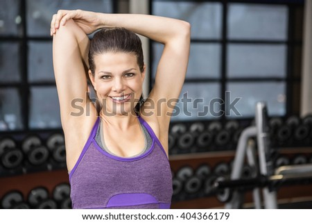 Smiling brunette stretching her arms at the gym - stock photo