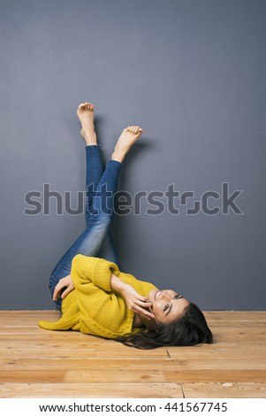 Smiling brunette talking on phone while lying on floor with barefoot legs on grey wall