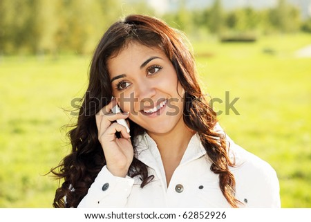 Smiling brunette talking on white cellphone closeup outdoors photo - stock photo