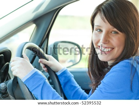 Smiling brunette teen girl using a mobile phone while driving - stock photo
