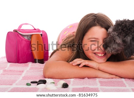 smiling brunette teenage girl in swimsuit at the beach getting a kiss from her shipoo dog (studio setting with beach and personal items) isolated on white background - stock photo