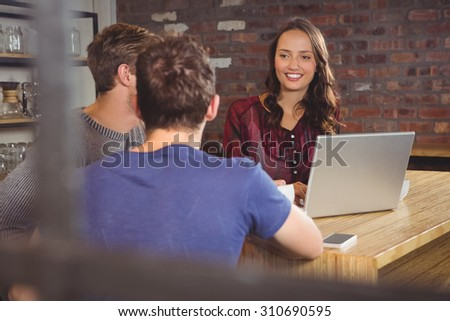 Smiling brunette using laptop and looking at her friends at coffee shop