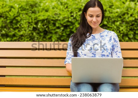 Smiling brunette using laptop on bench in the park - stock photo