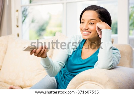 Smiling brunette using remote on the sofa
