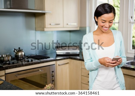 Smiling brunette using smartphone in the kitchen - stock photo