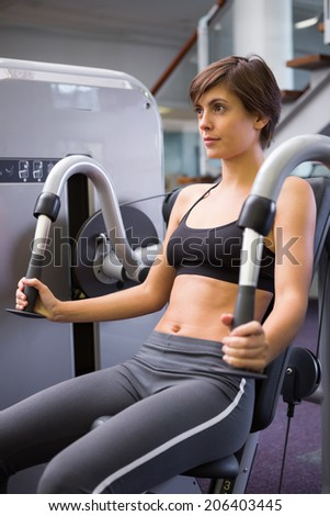 Smiling brunette using weights machine for arms at the gym - stock photo