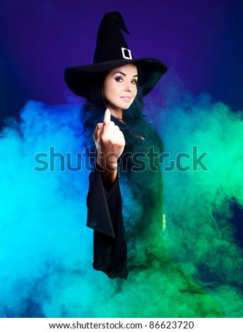 smiling brunette witch with clouds of smoke around her,calling us to come up,  isolated against white background - stock photo