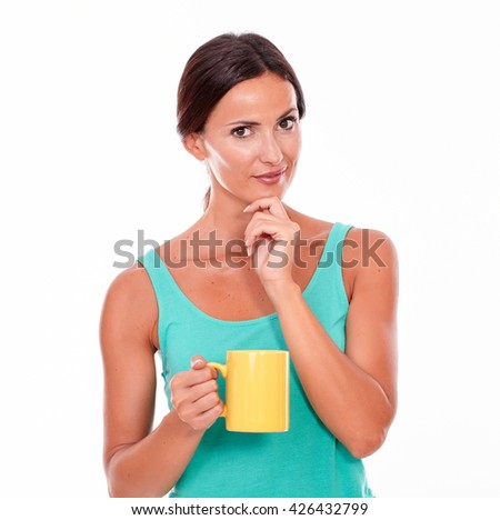 Smiling brunette with a coffee mug looking at camera with her hand on chin wearing a green tank top and her hair tied back, isolated - stock photo
