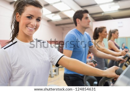Smiling brunette with other people on a step machine in gym - stock photo