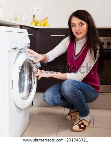 Smiling brunette woman cleaning washing machine at home - stock photo
