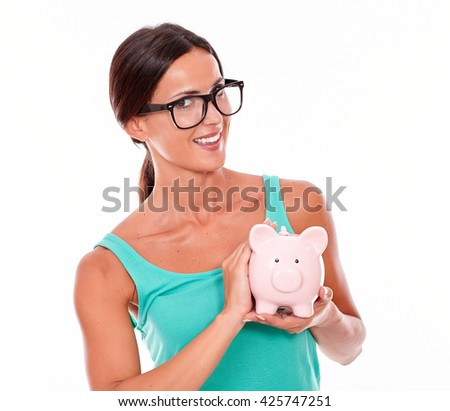 Smiling brunette woman holding pink piggy bank with both hands while looking at camera with glasses and a green tank top on a white background