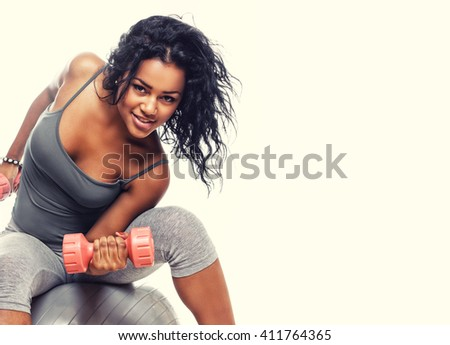 Smiling brunette woman in grey sportswear sits on fitness ball and holds small dumbells. - stock photo