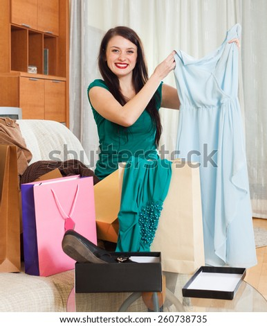 Smiling brunette woman with new blue dress at  home
