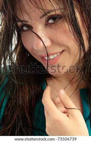 Smiling brunette woman with semi wet hair tousled loosely around her face and staring into the camera. - stock photo
