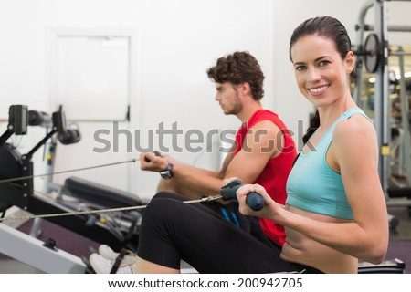Smiling brunette working out on the rowing machine at the gym - stock photo