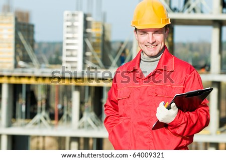 smiling builder worker inspector with clipboard in front of building under construction