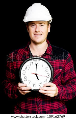 Smiling building workman holding a round clock showing five pm home time as he prepares to knock off from his shift at work