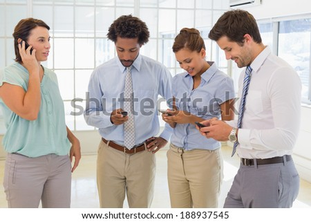 Smiling business colleagues text messaging in the office - stock photo