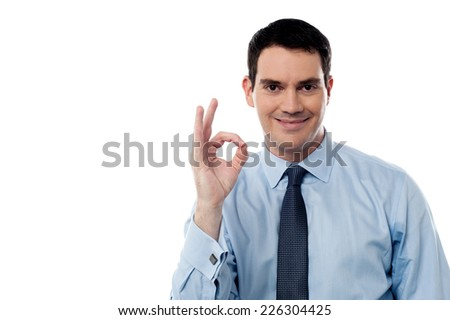 Smiling business executive with ok hand gesture - stock photo
