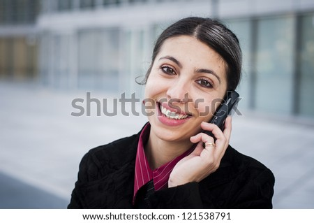 smiling business girl on the phone in front of a modern building