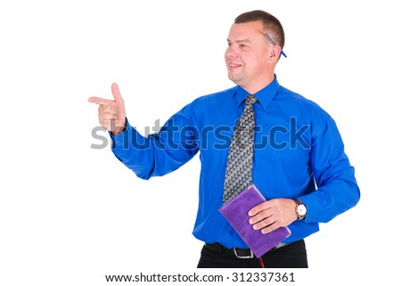 Smiling business guy holding organizer. Successful businessman in blue shirt and tie with notebook in hand looking a side and shows finger left. Isolated white background, Concept of leadership - stock photo