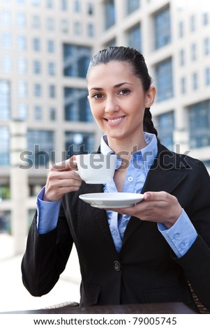 smiling business lady drinking coffee in business center - stock photo