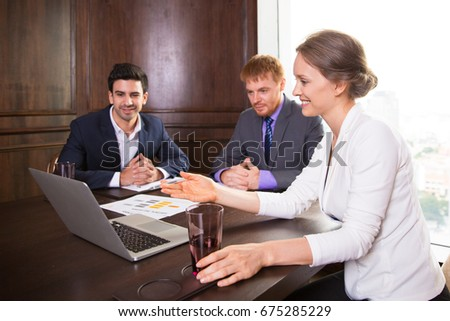 Smiling business lady showing presentation to colleagues