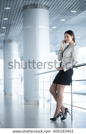 Smiling Business Lady Talking on Phone in Hall