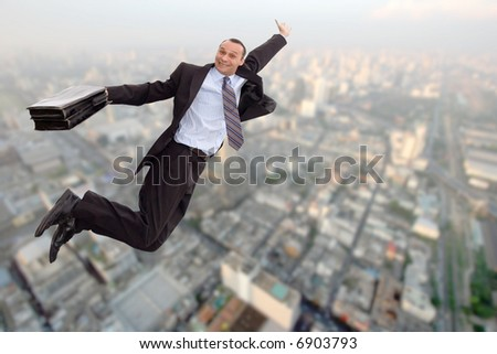 smiling business man flying over a big city