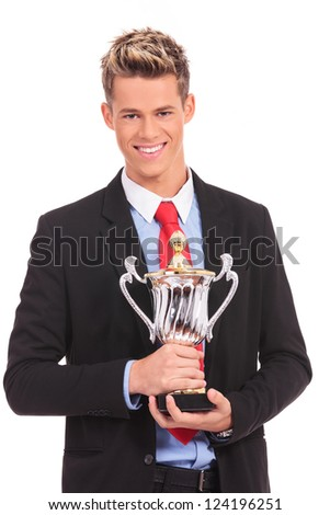 smiling business man in suit with win cup in hand