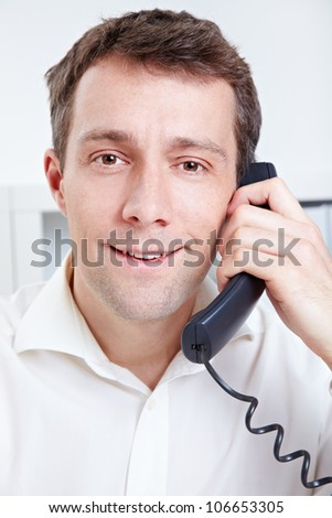 Smiling business man making phone call in the office - stock photo