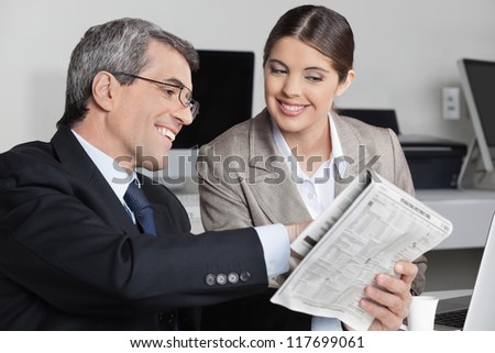 Smiling business man showing his assistent a newspaper story in the office - stock photo