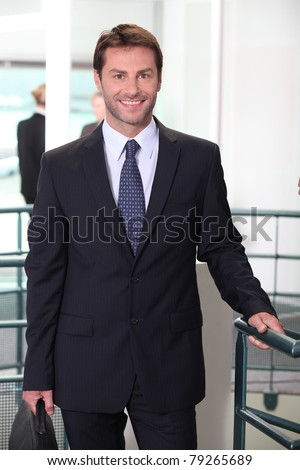 Smiling business man standing in an office building - stock photo